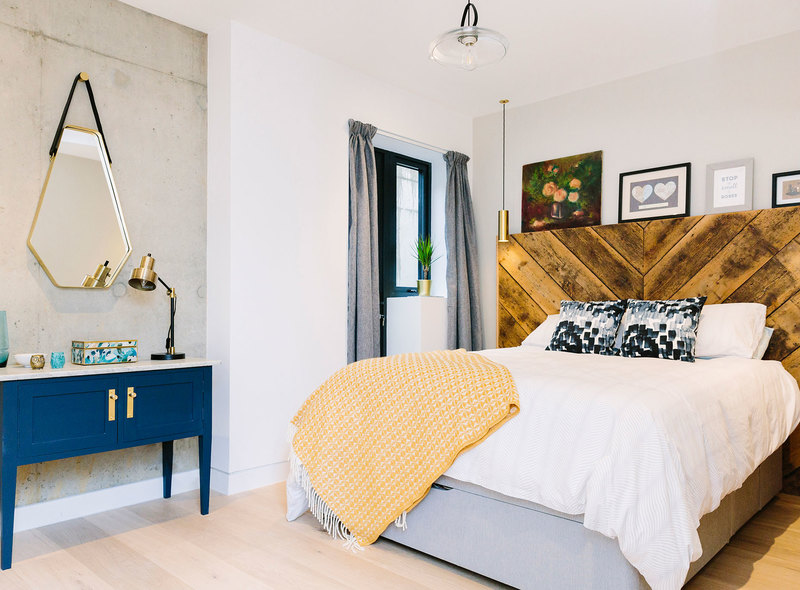 Oversized wooden headboard in an eclectic bedroom with brass, blue and yellow accents