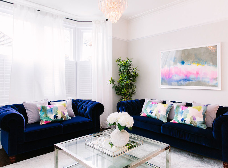 Navy velvet chesterfield sofas in a Victorian living room and silver glass coffee table and abstract art