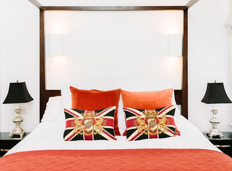 Traditional lamps, union jack flag cushions, patriotic red and a four poster bed for a traditional bedroom
