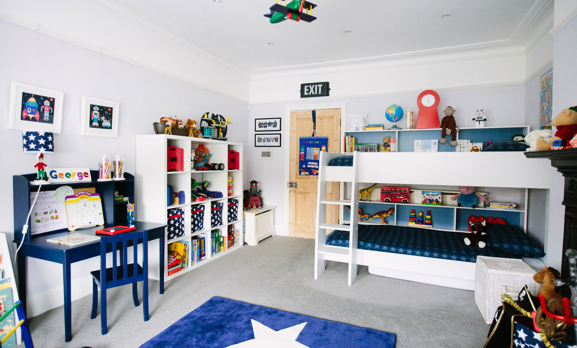 Navy desk and white bunk beds in a childrens bedroom