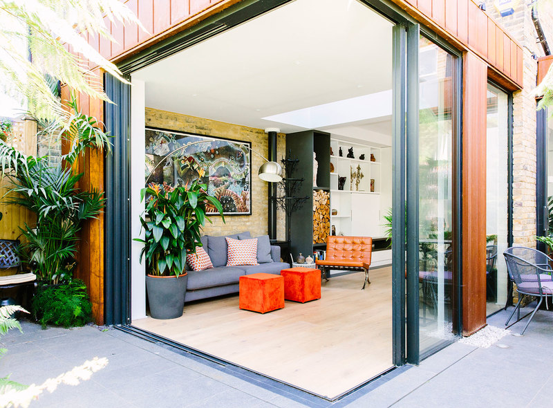 Sliding bi-fold glazing doors connecting the indoors and outdoors with indoor greenery and exposed brick wall