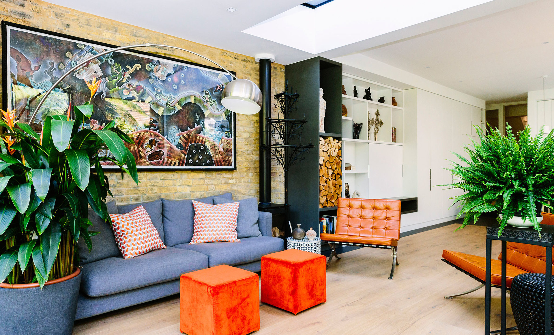 Pops of orange add colour to an organic light and bright living room with indoor greenery