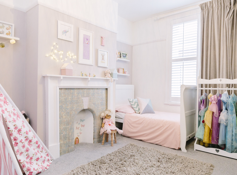 A baby pink little girl's children's bedroom with wall stickers and a teepee for playtime