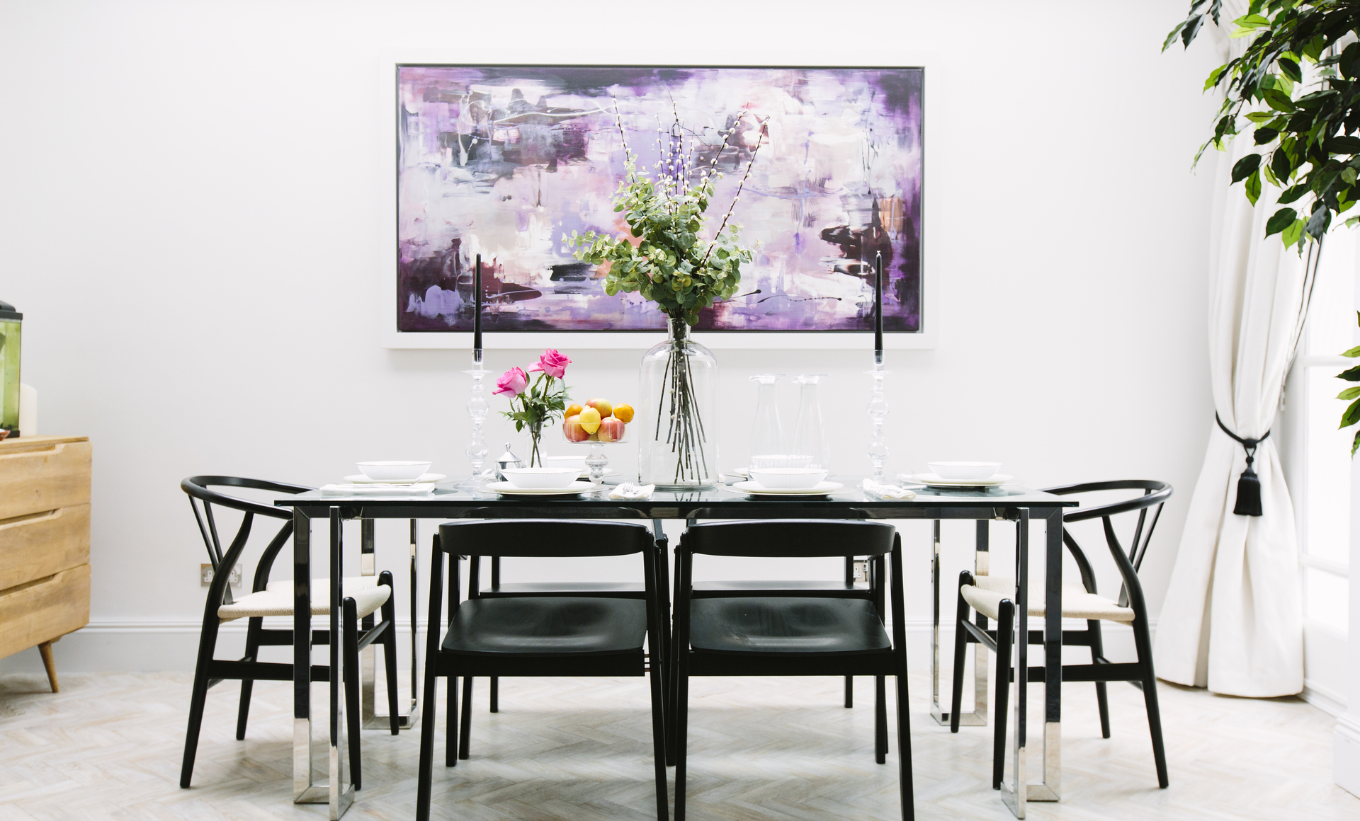 Elegant dining room in classic modern style with a glass dining table and wishbone chairs and purple abstract art
