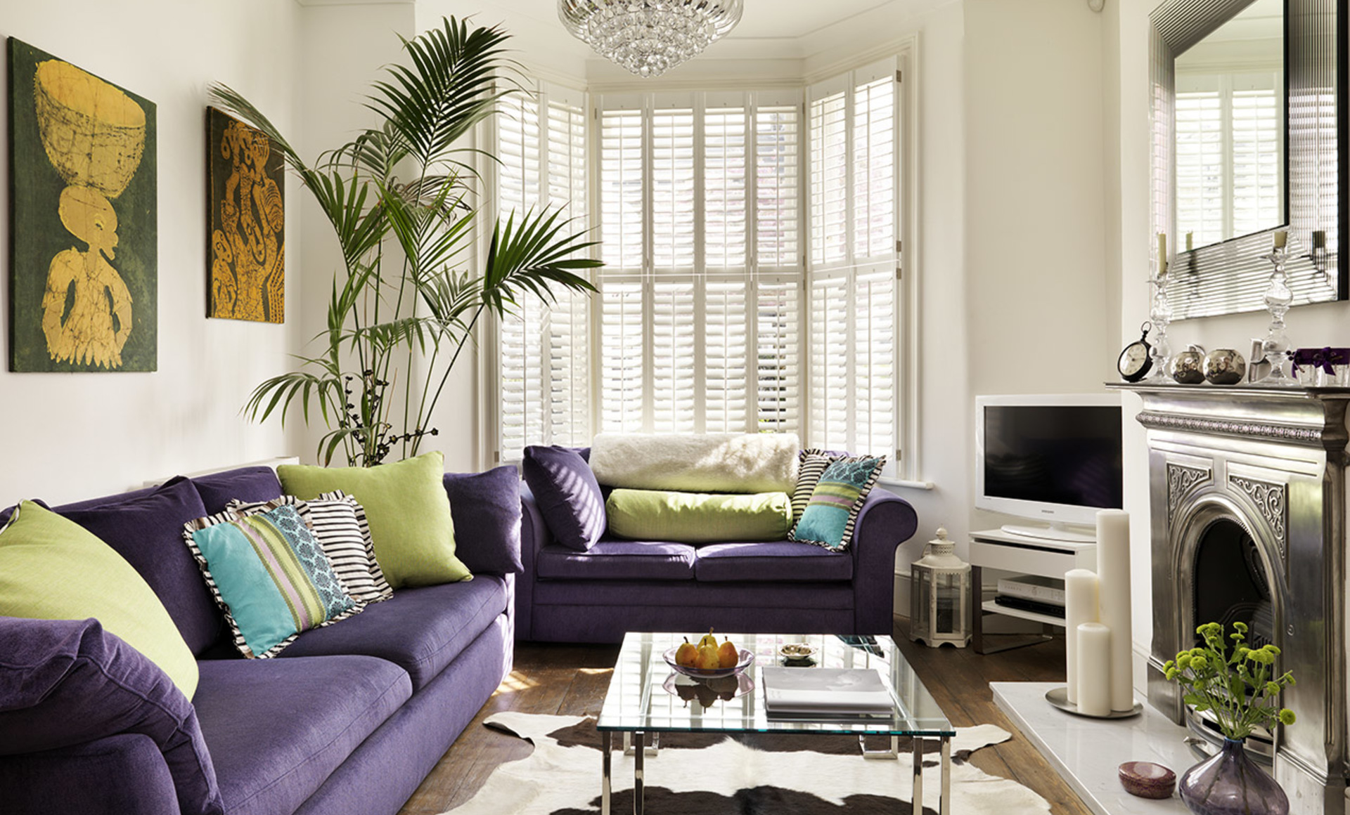Purple sofas in a Victorian living room with glass and silver furniture and accessories and indoor greenery