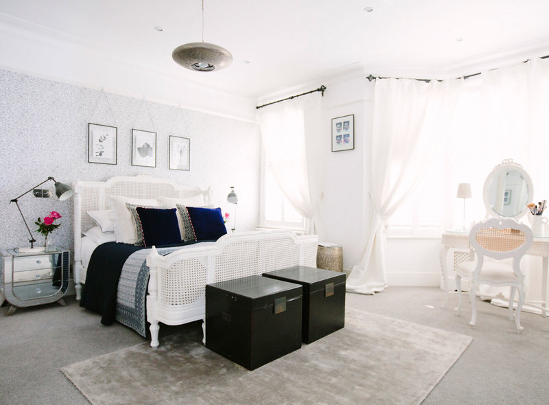 Mirrored bedside tables with classic style white rattan bed in a light and bright master bedroom