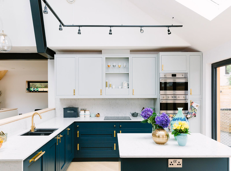 Marble worktops and blue cabinets and brass handles and knobs for an affordable but expensive looking kitchen