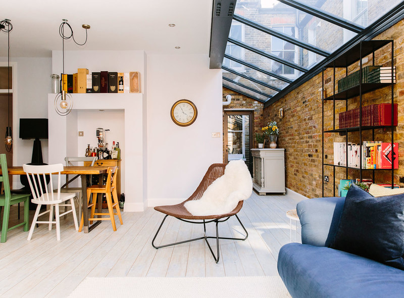 Living and dining open plan space with eclectic mix and match dining chairs and exposed brick wall