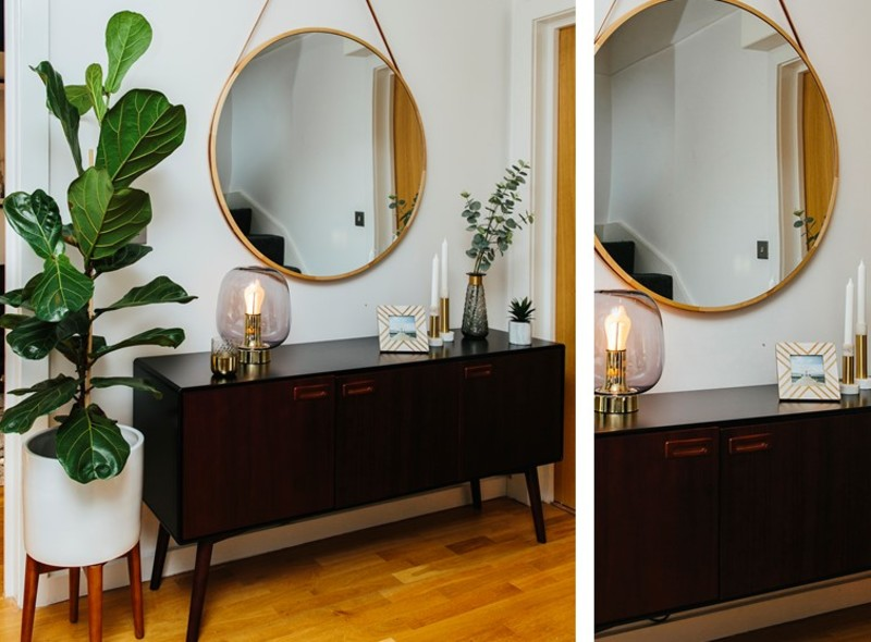 A dark wood mid-century sideboard with a large round mirror and indoor greenery in a hallway design