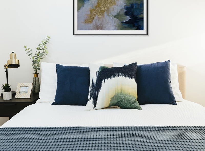 Navy, teal and brass bedroom with scatter cushions, brass lamp, indoor greenery and statement abstract art