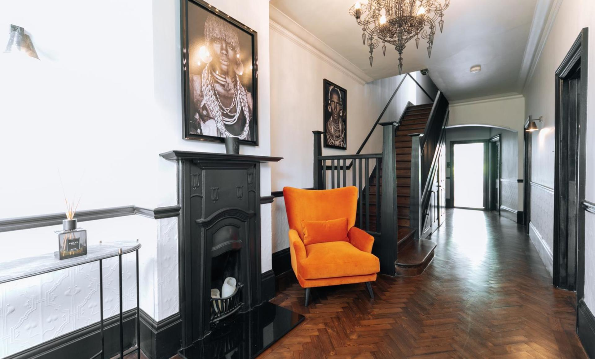 A grand entryway hallway with parquet flooring and dark fireplace and orange chair and chandelier and console