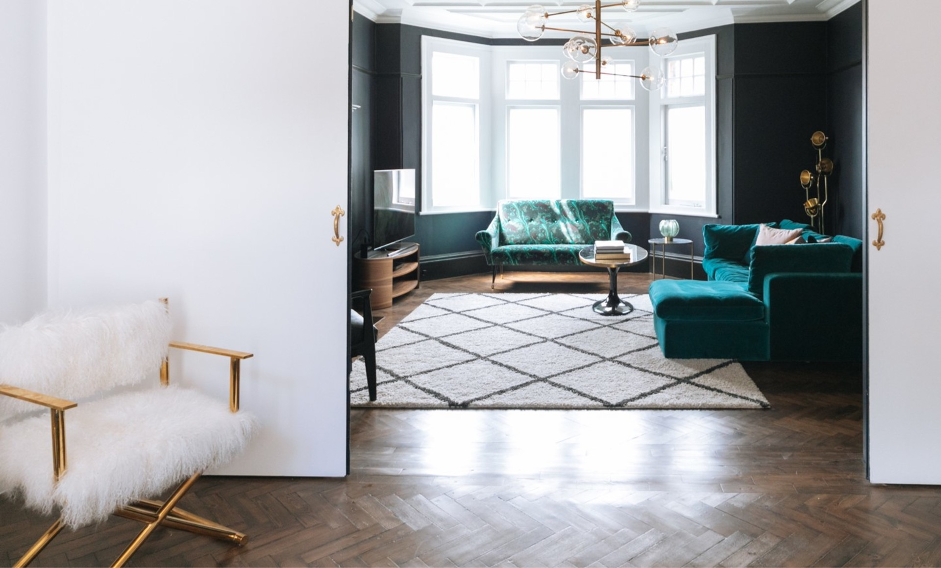 A fur statement directors chair in front of a dramatic and dark living room with deep teal velvet sofas and geometric rug