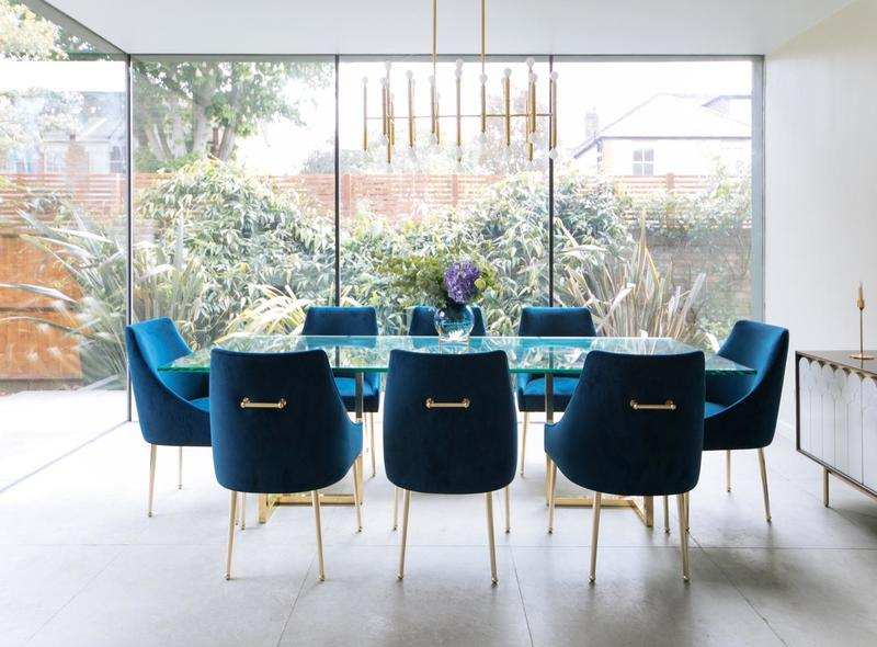 Glass and brass dining table with blue velvet upholstered dining chairs and a statement sideboard and gold chandelier